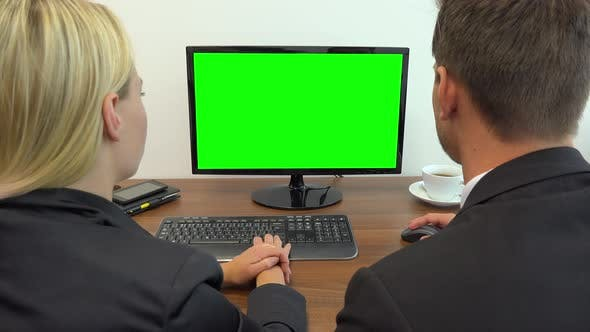 Thumbnail for Two Office Workers Sit at A Desk and Talk, the Man Works on A Computer with A Green Screen