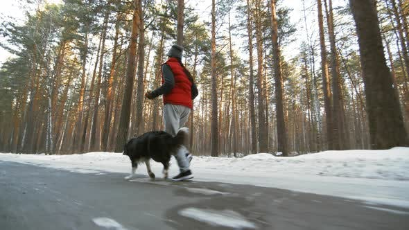 Thumbnail for Woman and Dog Running on Road in Woods