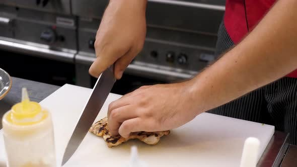 Thumbnail for Cook Hands Cutting a Piece of Fried Chicken Breast Meat