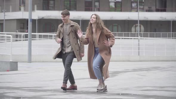 Thumbnail for Wide Shot of Cheerful Young Couple Dancing Outdoors on Urban City Street