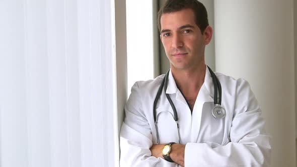 Confident male doctor standing by window