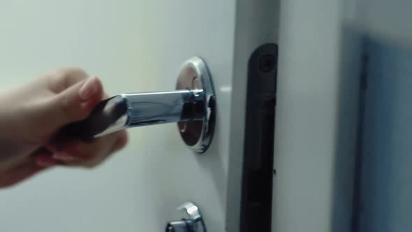 Quelqu' un ouvre la porte avec une poignée de porte