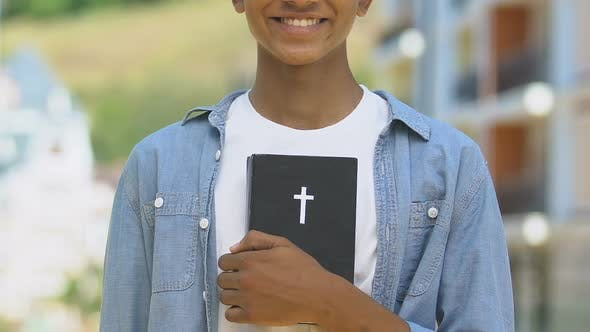 Thumbnail for Happy Teenage Boy Holding Bible