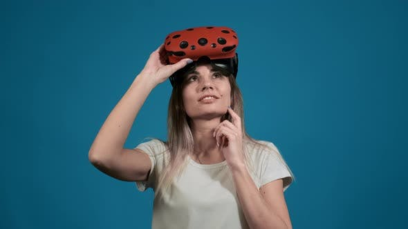 Thumbnail for Thoughtful Lady with Virtual Reality Goggles on Head on Blue
