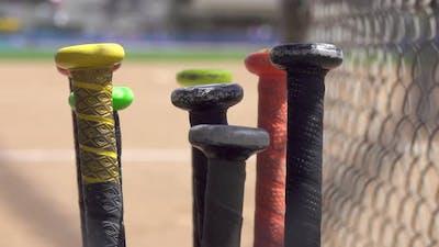 Details of bat handles at a little league baseball game.