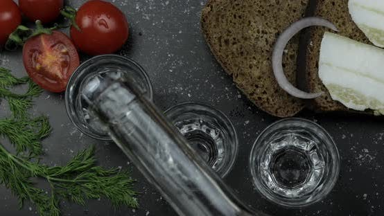 Thumbnail for Pour Alcohol Drink Vodka From a Bottle in Three Shot Glass. Surface with Snacks