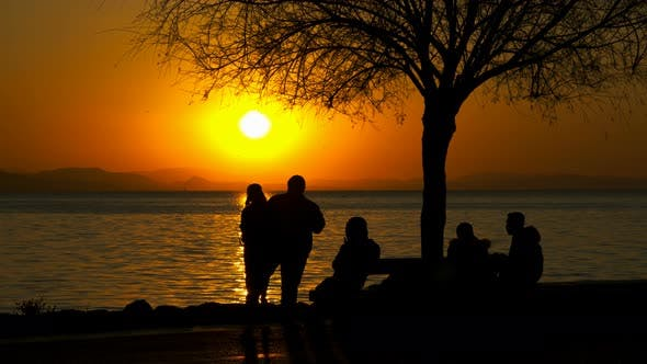 People Silhouette Near The Sea In Sunset