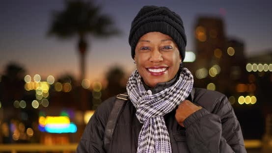 Thumbnail for An older black woman in warm clothes downtown at night