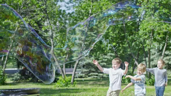 Thumbnail for Man Blowing Giant Soap Bubble at Performance for Kids in City Park