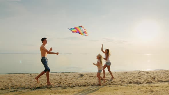 Cover Image for Adults and Children Play with a Kite on the Beach. Against the Backdrop of the Scenic Sky, Painted