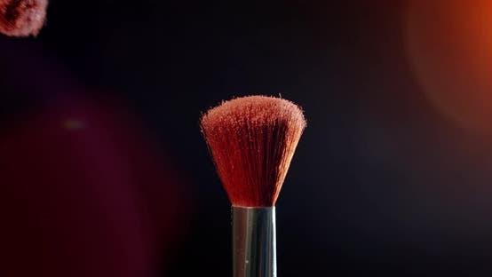 Thumbnail for Zwei Make-up-Pinsel mit Puder auf schwarzem Hintergrund mit Sonnenlicht Farbmalkonzept Zeitlupe.