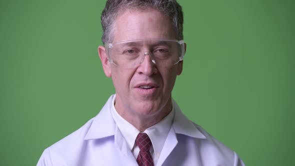 Thumbnail for Mature Man Doctor with Protective Glasses Having an Interview