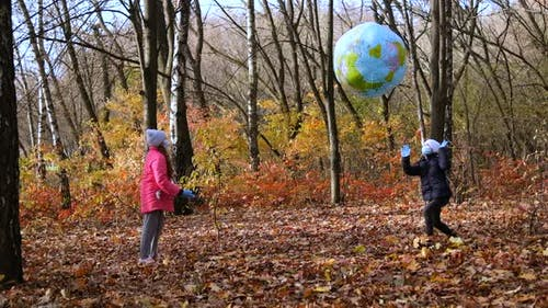 Two girls in medical masks play in the autumn Park with a large inflatable ball.