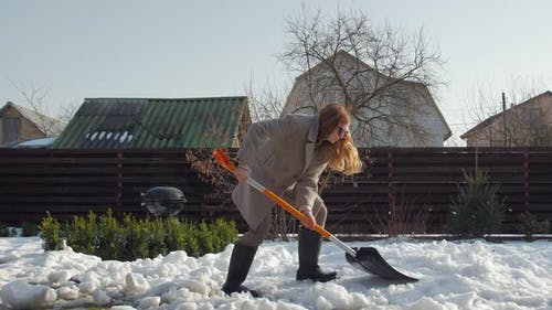 Woman Cleans Snow With Shovel