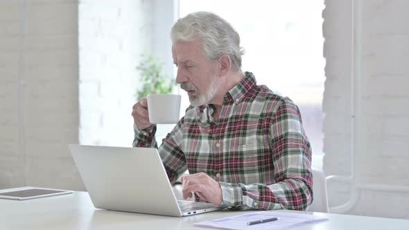 Hardworking Casual Old Man Drinking Coffee and Working