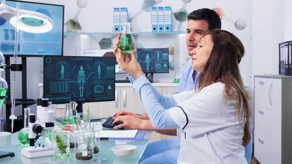 Bio Researcher Looking at Samples and Talking with Her Assistant