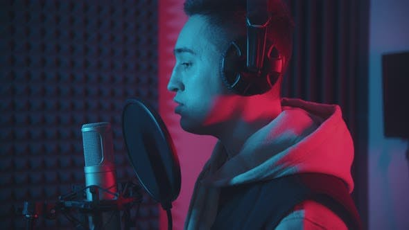 A Man in Headphones Rapping Through the Pop-filter in the Microphone - Studio in Neon Lighting