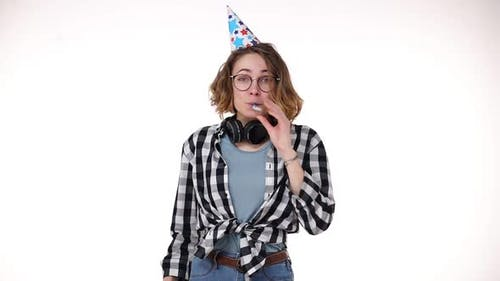 Portrait of Excited Young Woman in Plaid Shirt and Headphones on Neck in Birthday Colorful Hat Blow