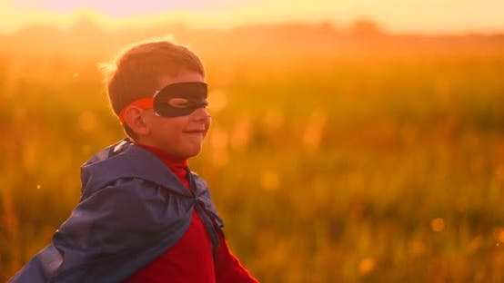 Thumbnail for The Boy in the Mask and Cape of a Super Hero at Sunset in a Field