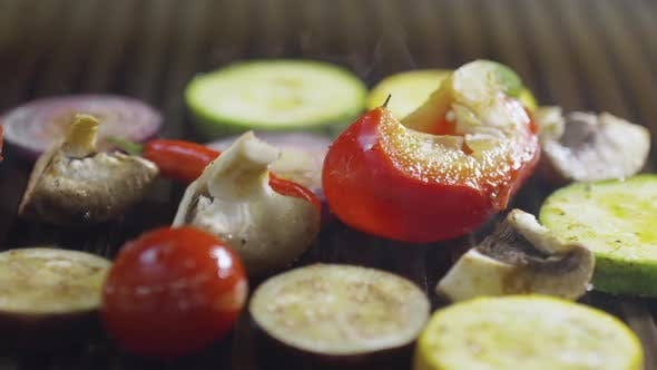 Cover Image for Pieces of Tomato, Champignon, Onion, Eggplant, Zucchini and Chili Pepper being Smoked on Grill