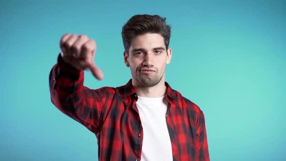 Cover Image for Young Handsome Man Standing on Blue Studio Background Showing Thumb Down Gesture