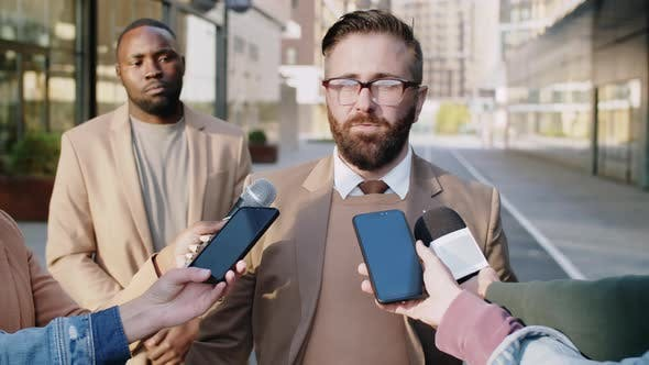 Man Giving Interview to TV Journalists Outdoors on Street