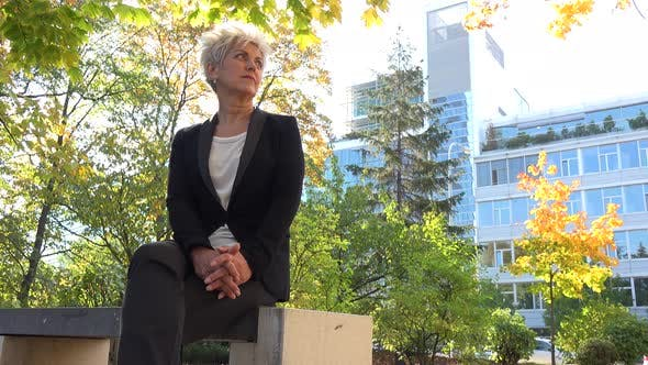 Thumbnail for A Middle-aged Businesswoman Sits on a Bench in a Park and Looks Around - an Office Building