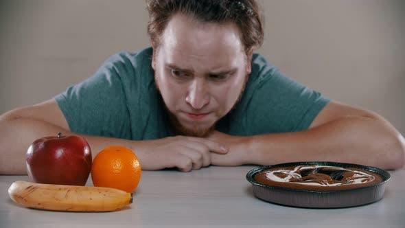 Thumbnail for Der Mensch wählt zwischen Kuchen und Früchten auf dem Tisch