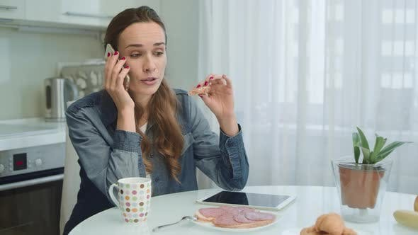 Thumbnail for Woman Talking on Phone While Eating Breakfast. Girl Eating Tasty Sandwich