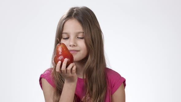 Thumbnail for A Little Girl on a White Background Holds in His Hand a Ripe Fragrant Pear. The Girl Bites and Eats
