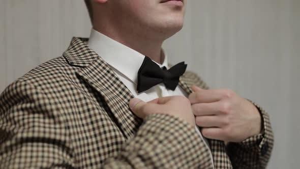 Thumbnail for Schöner Bräutigam trägt eine braune Jacke in einer Zelle. Hochzeits-Morgen. Geschäftsmann. Zeitlupe