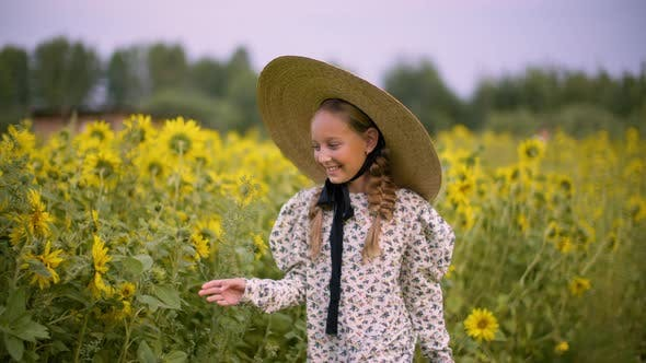 Thumbnail for Smiling Teenager Girl in Hat Touching Sunflowers on Summer Walk at Rustic Field. Happy Young Girl