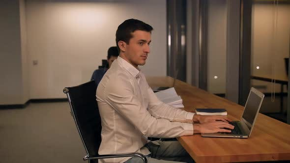 Handsome Young Man Writes in a Notebook Looks at the Monitor in Office and Than Look To the Camera