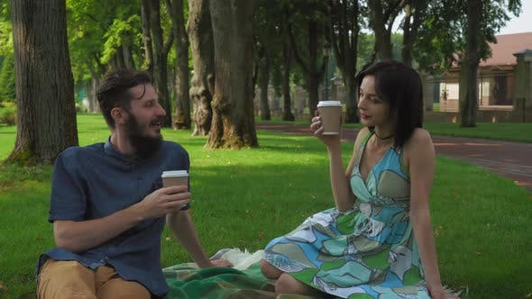 Thumbnail for A Young Boy and Girl Held a Meeting and Picnic in the Park. They Talk and Drink Coffee While Sitting