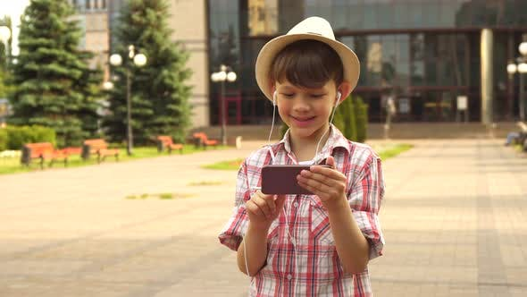 Thumbnail for Little Boy Listens To Music on His Smartphone