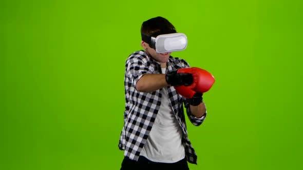 Cover Image for Mann spielt in einer Box mit VR-Brille. Grüner Bildschirm