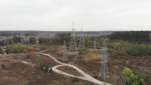 Transmission electricity steel pylon towers. High voltage electric towers in forest.