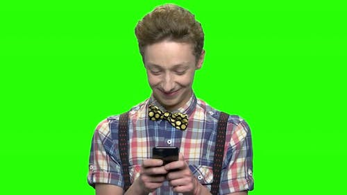 Teen Boy in Fashionable Clothes Texting on Mobile Phone