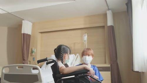 Asian scrub uniform nurse taking care of girl kid patient sitting on wheelchair in hospital ward.