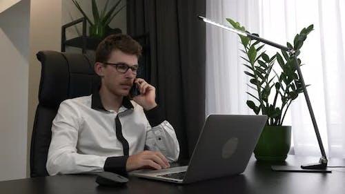 Focused man in eyeglasses is speaking by mobile phone in his modern business office.