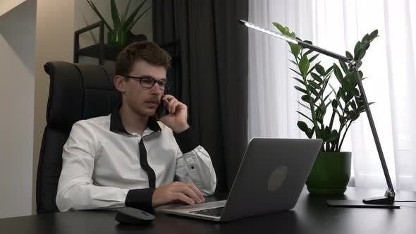 Thumbnail for Focused man in eyeglasses is speaking by mobile phone in his modern business office.
