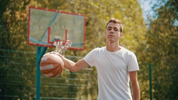 Thumbnail for A Young Man in White T-shirt Standing on a Sports Ground and Discards the Ball From the Floor