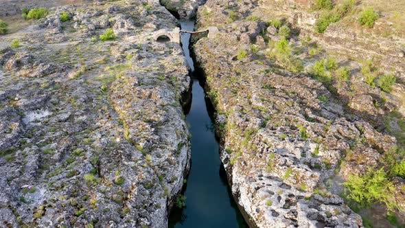 Narrow mountain river flowing through rocky landscape, Stream bed cut deep into stones