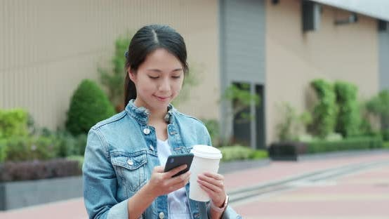 Woman use of mobile phone and holding coffee cup