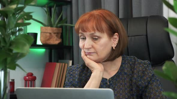 Thumbnail for Thoughtful woman is sitting at workplace desk with laptop computer