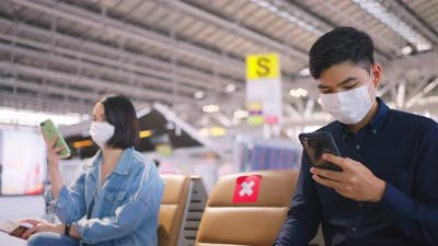 Social distancing, two people wearing face mask sit keeping distance away in airport terminal.