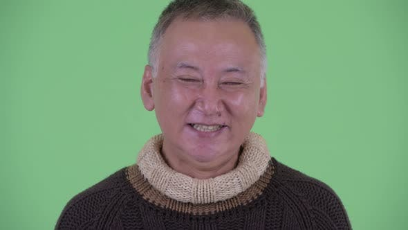 Thumbnail for Face of Happy Mature Japanese Man Smiling and Laughing Ready for Winter