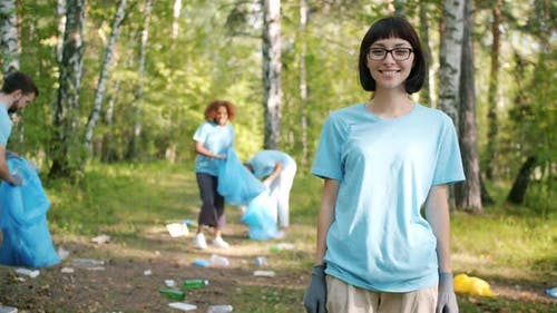 Modern Young Woman Eco-activist Turning To Camera in Forest Smiling Outside