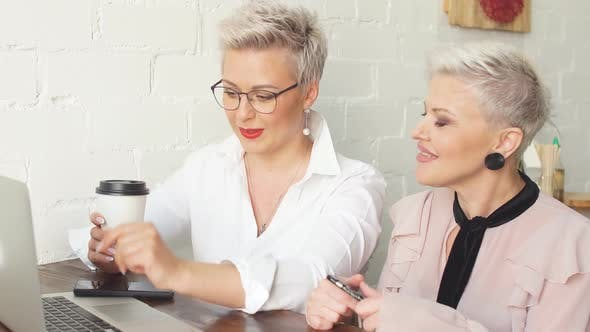 Thumbnail for Two Older Friends of a Business Lady Discuss a Business Idea Sitting in a Cafe