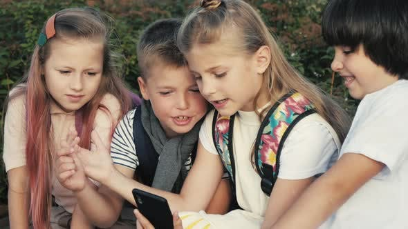 Thumbnail for Fun with Phone. Two Little School Girls and Two Boys Using Smart Phone.